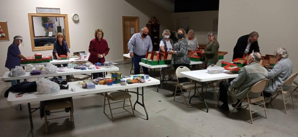 Picture of our church members packing shoeboxes for the 2020 Operation Christmas Child