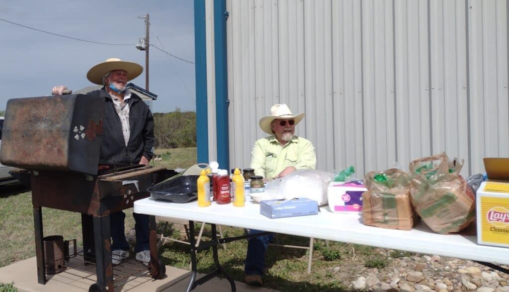 "Picture of two church members preparing ""tube steaks"""